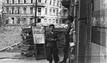 """cywile przy barykadzie na ul. Koszykowej - tablica ostrzega przed """"gołębiarzami"""" (niemieckimi snajperami)/fot. arch."""